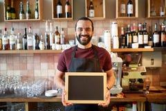 Uomo o cameriere felice con l'insegna della lavagna alla barra Fotografia Stock