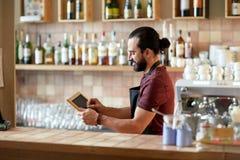 Uomo o cameriere felice con l'insegna della lavagna alla barra Immagine Stock Libera da Diritti