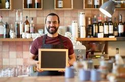 Uomo o cameriere felice con l'insegna della lavagna alla barra Fotografie Stock