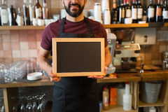 Uomo o cameriere felice con la lavagna in bianco alla barra Fotografie Stock