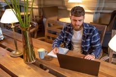 Uomo o free lance casuale di affari che progetta il suo lavoro sul taccuino, lavorante al computer portatile con lo Smart Phone,  Fotografia Stock