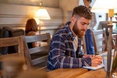 Uomo o free lance casuale di affari che progetta il suo lavoro sul taccuino, lavorante al computer portatile con lo Smart Phone,  Immagine Stock Libera da Diritti