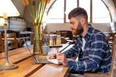 Uomo o free lance casuale di affari che progetta il suo lavoro sul taccuino, lavorante al computer portatile con lo Smart Phone,  Fotografia Stock Libera da Diritti
