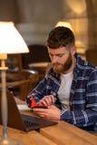 Uomo o free lance casuale di affari che progetta il suo lavoro sul taccuino, lavorante al computer portatile con lo Smart Phone,  Fotografie Stock
