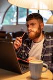 Uomo o free lance casuale di affari che progetta il suo lavoro sul taccuino, lavorante al computer portatile con lo Smart Phone,  Fotografie Stock Libere da Diritti