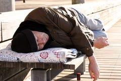 Uomo o rifugiato senza tetto che dorme sul banco di legno con la bottiglia immagine stock libera da diritti