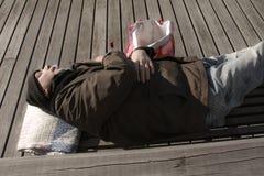 Uomo o rifugiato senza tetto che dorme sul banco di legno con la bottiglia immagine stock