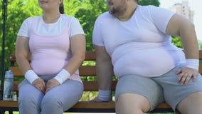 Uomo obeso coraggioso che si siede vicino alla ragazza paffuta in parco e che prova a fare la conoscenza stock footage