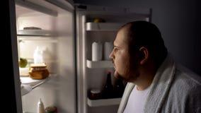 uomo obeso Debole-voluto che cerca lo spuntino in frigorifero alla notte, guasto di dieta fotografia stock