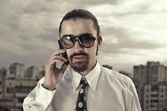 Uomo in occhiali da sole che comunica sul telefono mobile Fotografie Stock