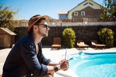 Uomo in occhiali da sole e cocktail bevente del cappello, sedentesi vicino allo stagno Immagine Stock