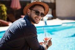 Uomo in occhiali da sole e cocktail bevente del cappello, sedentesi vicino allo stagno Immagini Stock Libere da Diritti