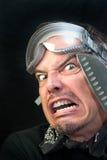 Uomo in occhiali di protezione con il coltello, impaurito Immagine Stock