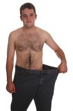 Uomo ora sottile che mostra fuori i suoi vecchi jeans fotografie stock libere da diritti