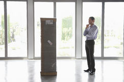 Uomo osservando pacchetto in ufficio vuoto Fotografie Stock Libere da Diritti