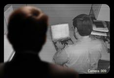 Uomo osservando un lavoro degli impiegati via un video monito a circuito chiuso Immagini Stock Libere da Diritti