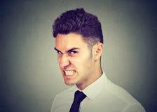 Uomo ostile di affari che esamina macchina fotografica con l'espressione arrabbiata del fronte immagine stock