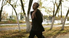 Uomo pacifico che corre e che ascolta la musica favorita tramite le cuffie Pareggiare di mattina il parco di verde nel nero archivi video
