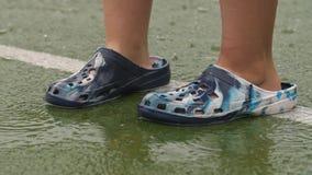 Uomo in pantofole di gomma nella pioggia stock footage