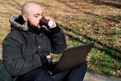 Uomo in parco che fa affare sul computer portatile e che beve caffè Immagine Stock Libera da Diritti