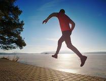 Uomo pazzo che salta mentre joogging nel lago della molla di mattina fotografia stock