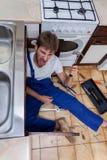 Uomo pazzo durante il rapair in cucina Fotografie Stock