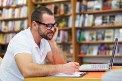Uomo pensieroso che lavora nella biblioteca Fotografie Stock