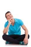 Uomo pensieroso che si siede e che guarda su Fotografia Stock
