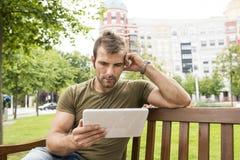 Uomo pensieroso con il computer della compressa che si siede nella via fotografie stock