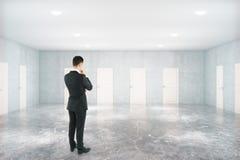 Uomo pensieroso nella sala con le porte Immagine Stock Libera da Diritti