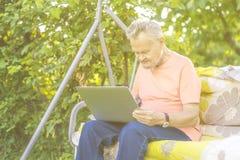Uomo pensionato anziano che lavora al computer nel giardino del cottage di estate fotografie stock
