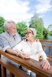 Uomo pensionato barbuto che celebra il suo compleanno con la moglie vicino al lago immagini stock