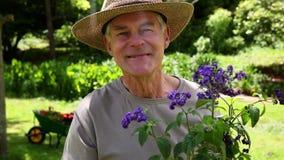 Uomo pensionato che fa il giardinaggio e che sorride alla macchina fotografica video d archivio