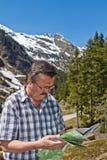 Uomo pensionato che fa un'escursione nelle alpi Immagine Stock