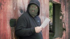 Uomo pericoloso con il coltello da cucina vicino alla parete della costruzione archivi video