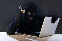 Uomo pericoloso del pirata informatico con il computer e la serratura che incidono sistema nel concetto cyber di crimine Fotografia Stock Libera da Diritti