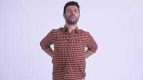 Uomo persiano barbuto sollecitato dei pantaloni a vita bassa che ha dolore alla schiena archivi video