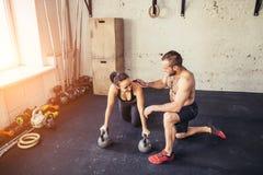 Uomo personale dell'istruttore della palestra allenamento della donna nell'esercizio di forma fisica Fotografie Stock