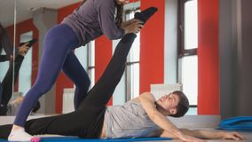 Uomo personale femminile di aiuto dell'istruttore con l'allungamento dell'esercizio davanti allo specchio Fotografia Stock Libera da Diritti