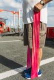 Uomo più anziano 80-89 che exercsing con un cavo di allungamento alla palestra dell'aria aperta Fotografia Stock