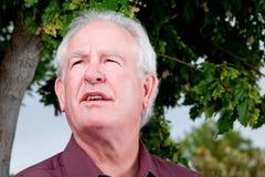 Uomo più anziano che osserva skyward con la preoccupazione immagini stock libere da diritti