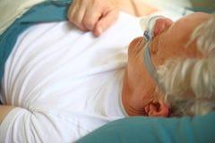 Uomo più anziano che per mezzo del dispositivo dell'apnea nel sonno fotografia stock