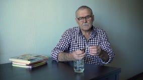 Uomo più anziano che prende medicina video d archivio