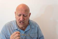 Uomo più anziano che tiene i vetri con afflitta chiusa degli occhi, calvo, alopecia, chemioterapia, cancro, isolato su bianco Fotografie Stock Libere da Diritti