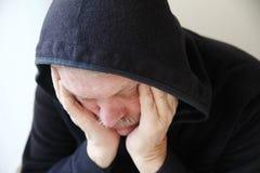 Uomo più anziano triste in rivestimento incappucciato immagini stock libere da diritti