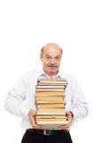 Uomo più anziano in una camicia bianca che tiene una pila pesante di libri Immagine Stock