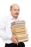 Uomo più anziano in una camicia bianca che tiene una pila pesante di libri Fotografia Stock Libera da Diritti