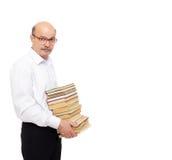 Uomo più anziano in una camicia bianca che tiene una pila pesante di libri Fotografie Stock Libere da Diritti