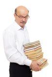 Uomo più anziano in una camicia bianca che tiene una pila pesante di libri Immagine Stock Libera da Diritti