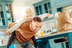Uomo piacevole allegro che gioca con suo figlio immagini stock